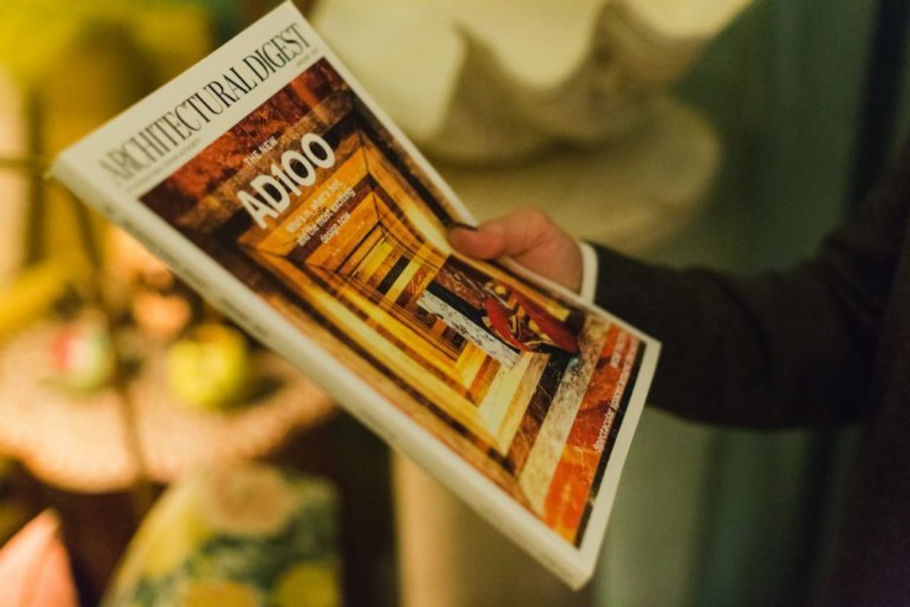 An ICAA Private New York Tour guest surveys the cover of Architectural Digest's January issue, featuring the work of Frank de Biasi (Image Source: Frank de Biasi)