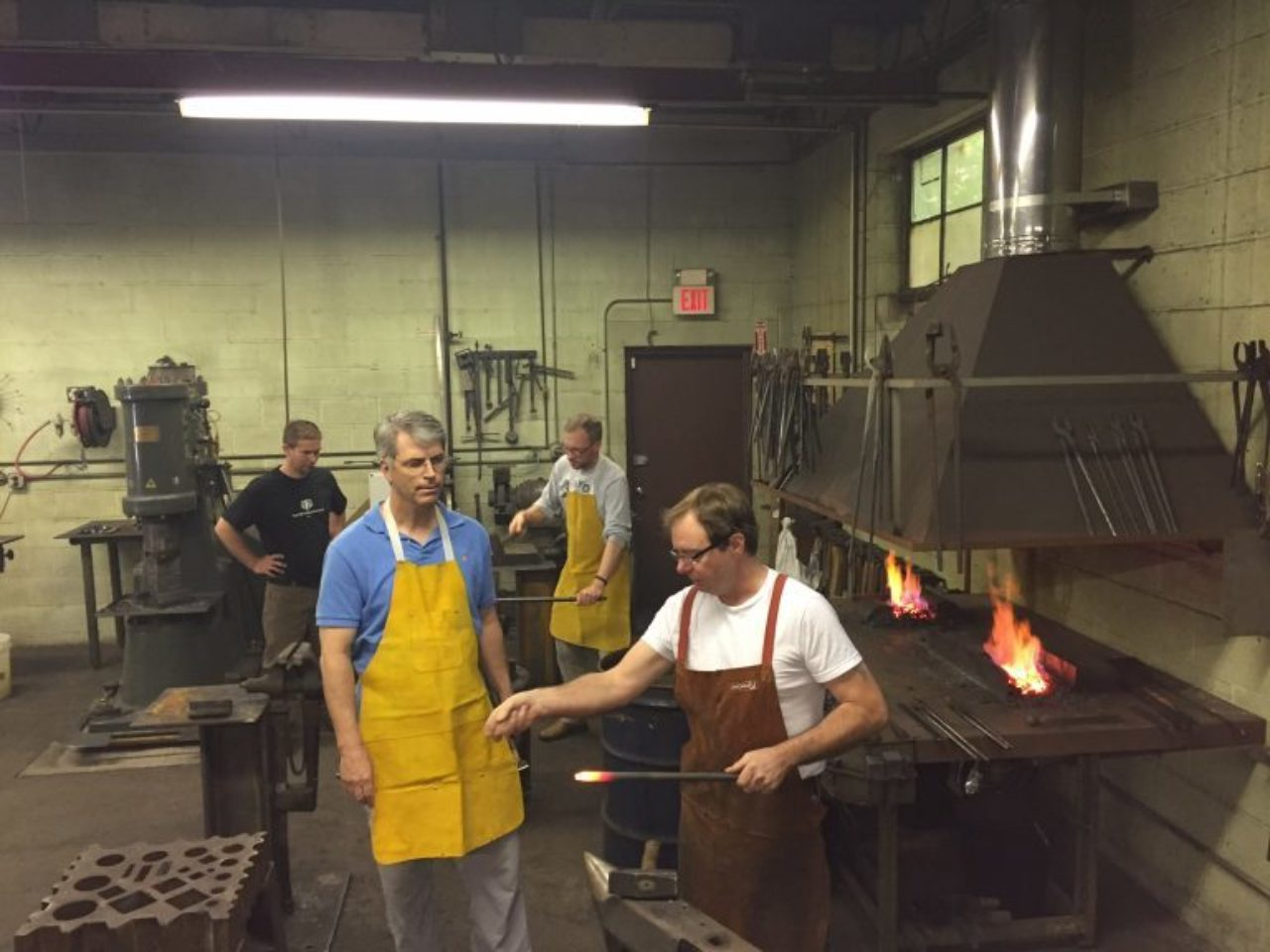 Close shows Foster Lyons how to forge iron.