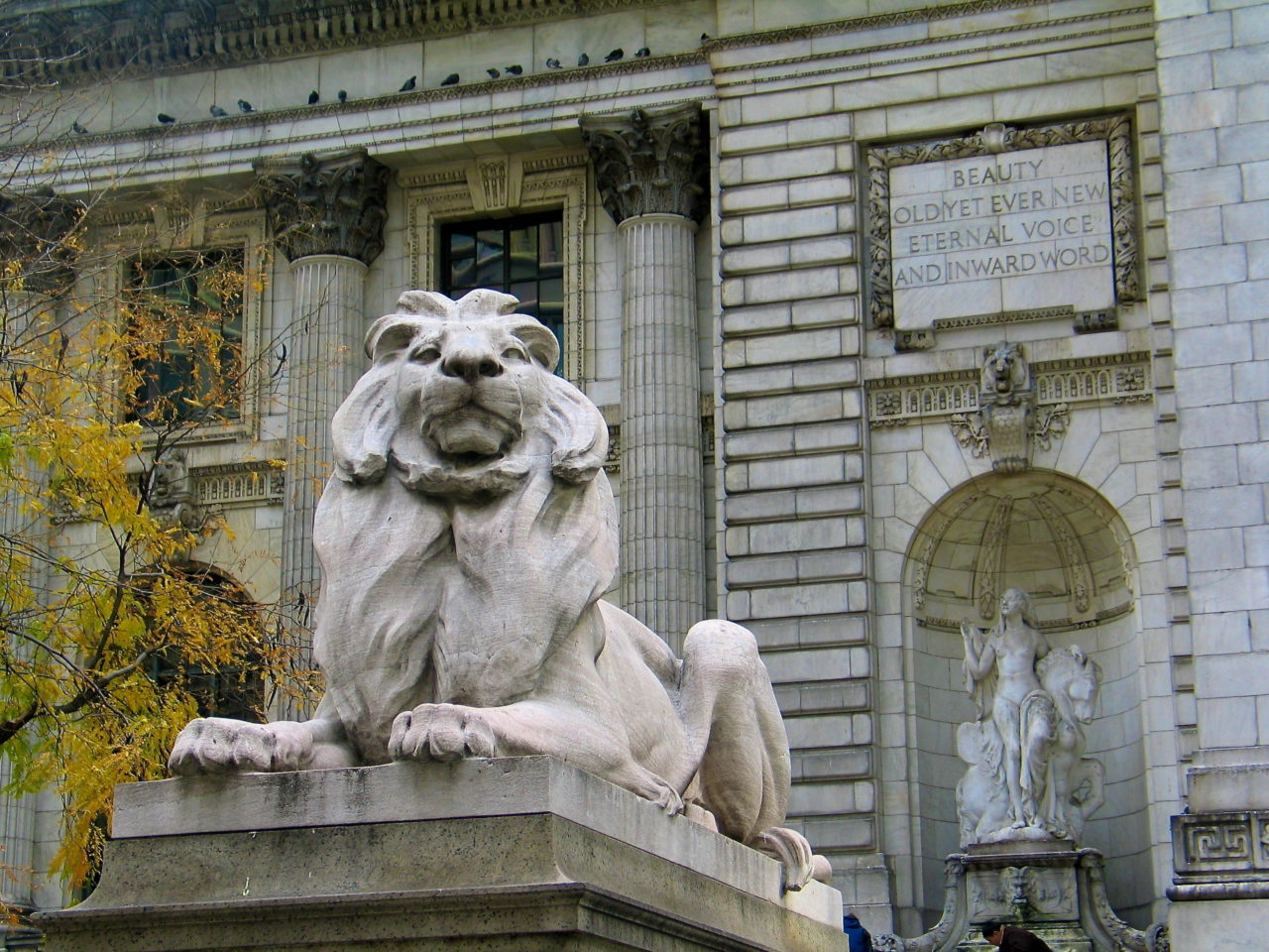 "The statuary of the New York Public Library - one of Edward Clark Potter's lions sits in the foreground, with  Frederick MacMonnies' sculptures depicting ""Beauty"" in the background"