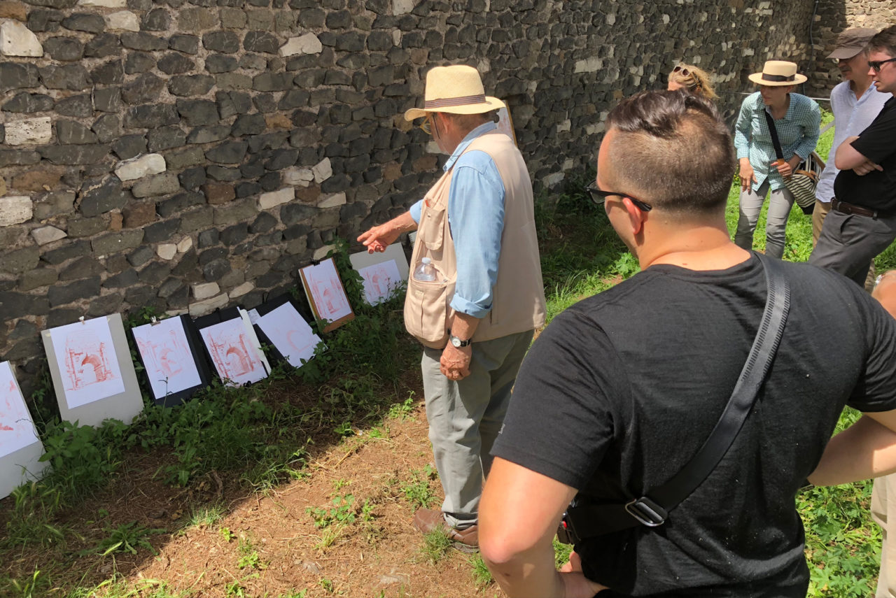 Tour participants review their sanguine pencil drawings of the Arch of Drusus
