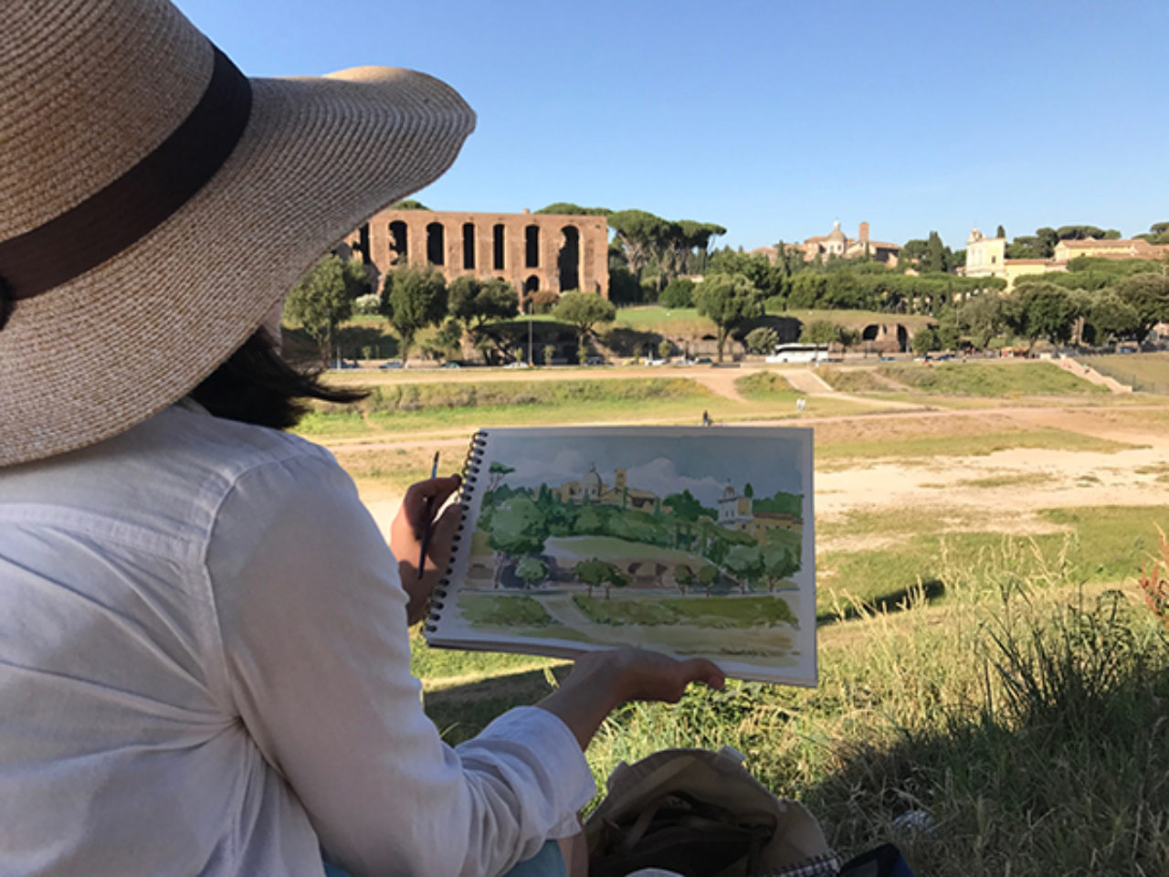 Tour participants sketch on location at Circus Maximus, overlooking Palatine Hill