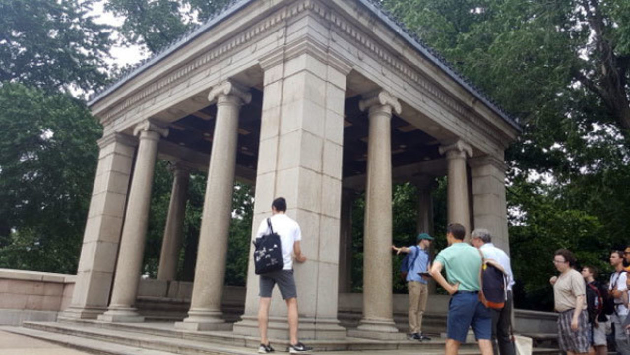 Students study a pavilion featuring ionic columns