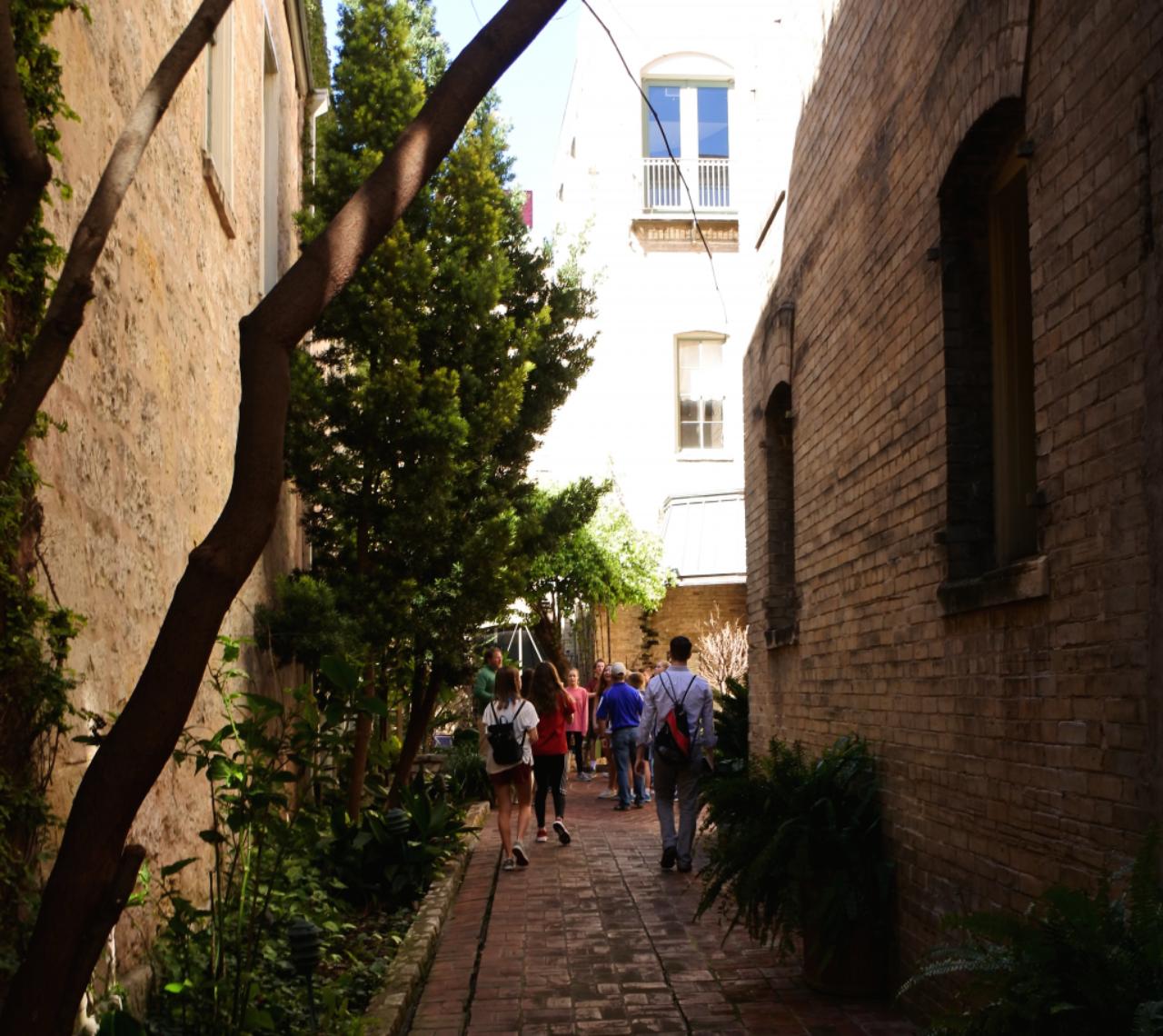 Mac White leads a walking tour into a courtyard