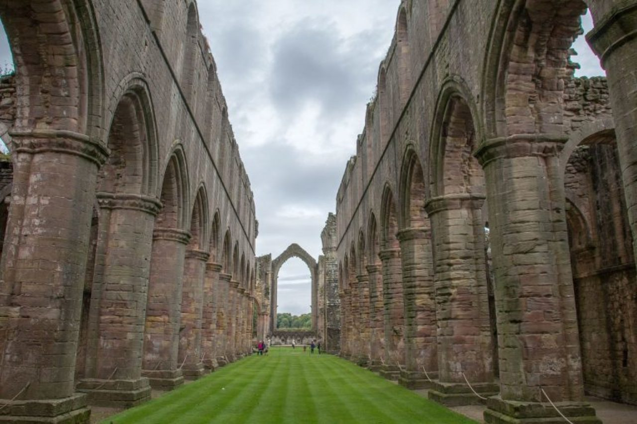 The ruins of Fountains Abbey, a former Cistercian monastery originally founded in the 12th Century (Image Source: Wikipedia / Mike Peel)