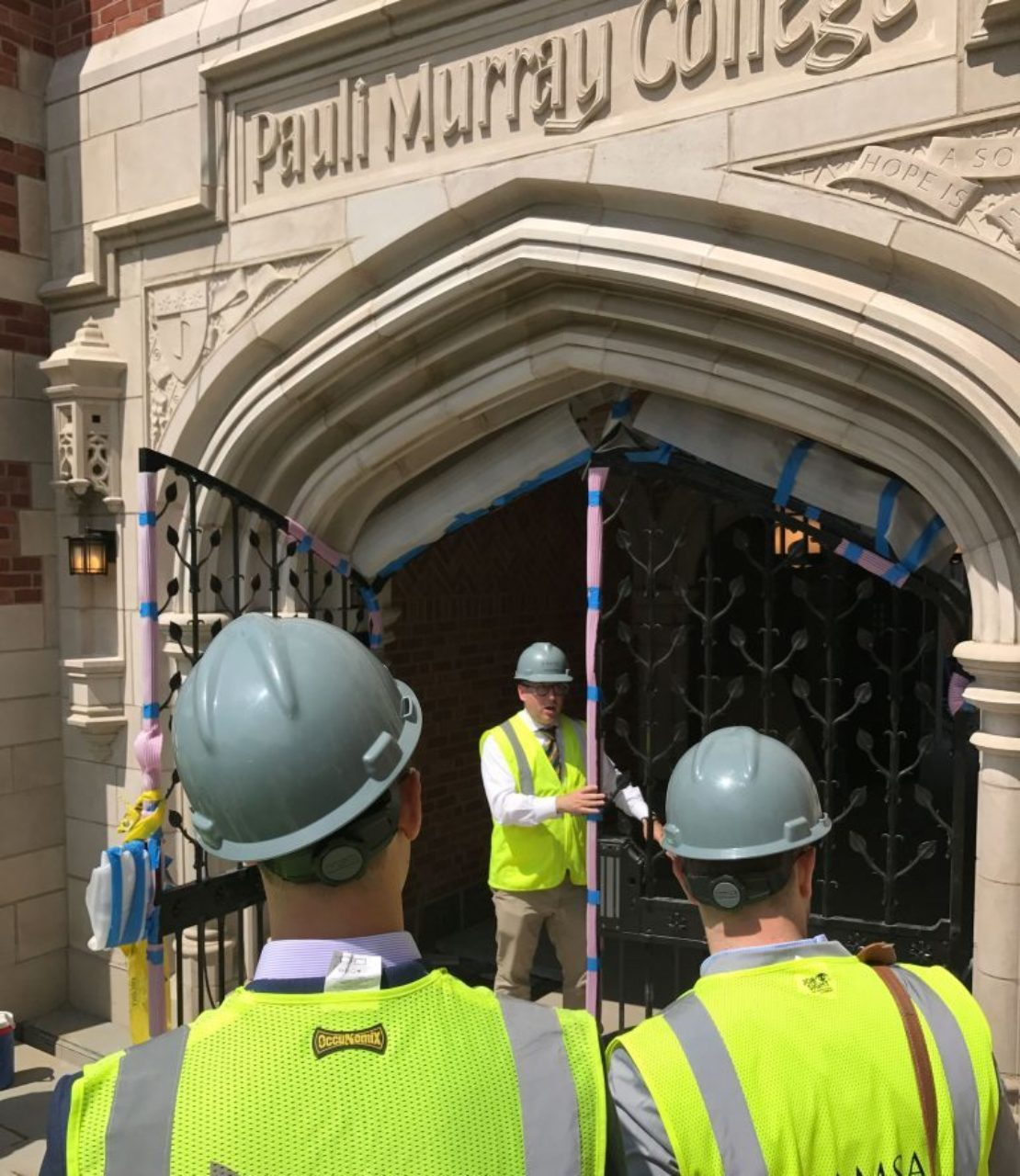 Tour participants inspect the ironwork in the gates at Pauli Murray College
