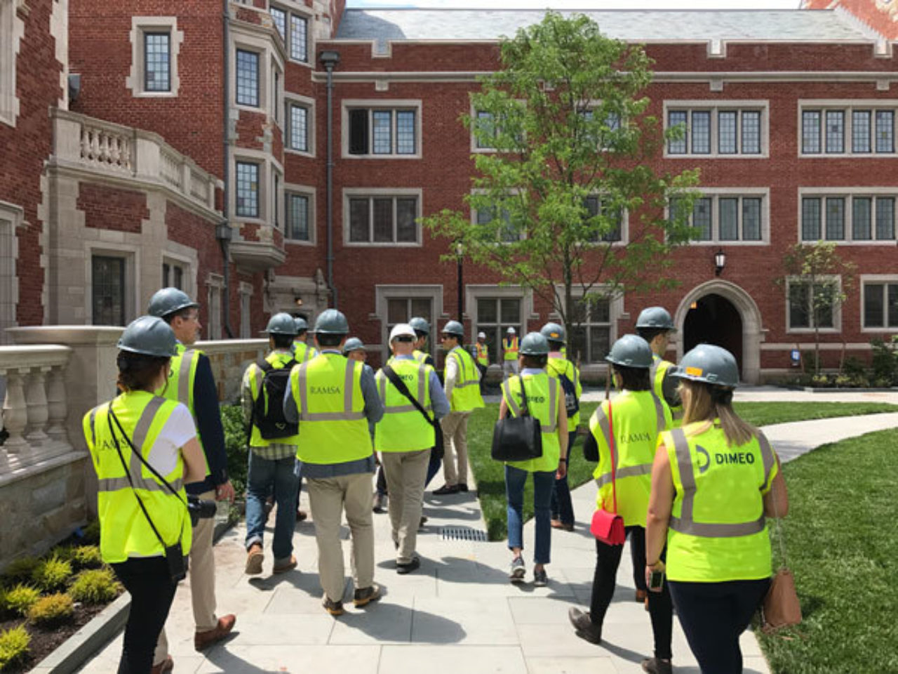 Tour participants cross through a courtyard while touring the new residential colleges